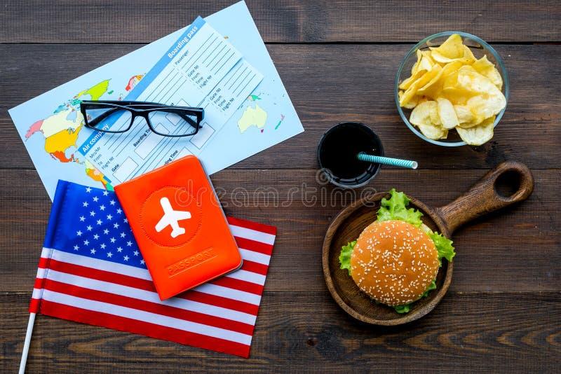 Hamburguesa, microprocesadores, mapa, boletos y bandera de los E.E.U.U. para el turismo gastronómico a América en la opinión supe imagen de archivo