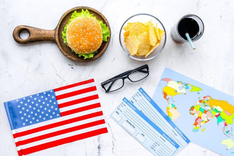 Hamburguesa, microprocesadores, mapa, boletos y bandera de los E.E.U.U. para el turismo gastronómico a América en la opinión supe fotografía de archivo