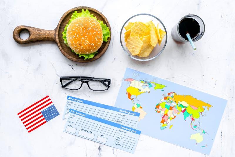 Hamburguesa, microprocesadores, mapa, boletos y bandera de los E.E.U.U. para el turismo gastronómico a América en la opinión supe imagenes de archivo
