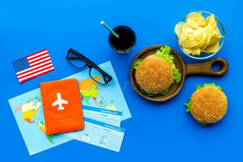 Hamburguesa, microprocesadores, mapa, pasaporte, boletos y bandera de los E.E.U.U. para el turismo gastronómico a América en la o imagen de archivo