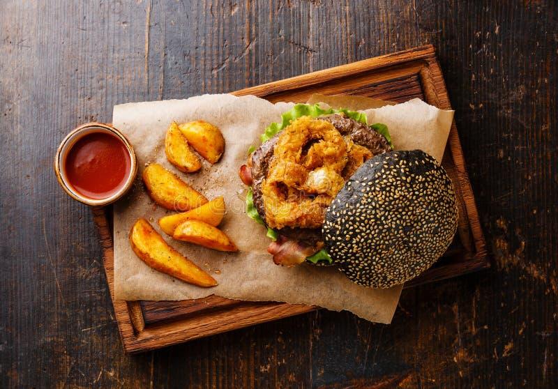 Hamburguesa negra con la carne, las fritadas de los anillos de cebolla y las cuñas de la patata imágenes de archivo libres de regalías