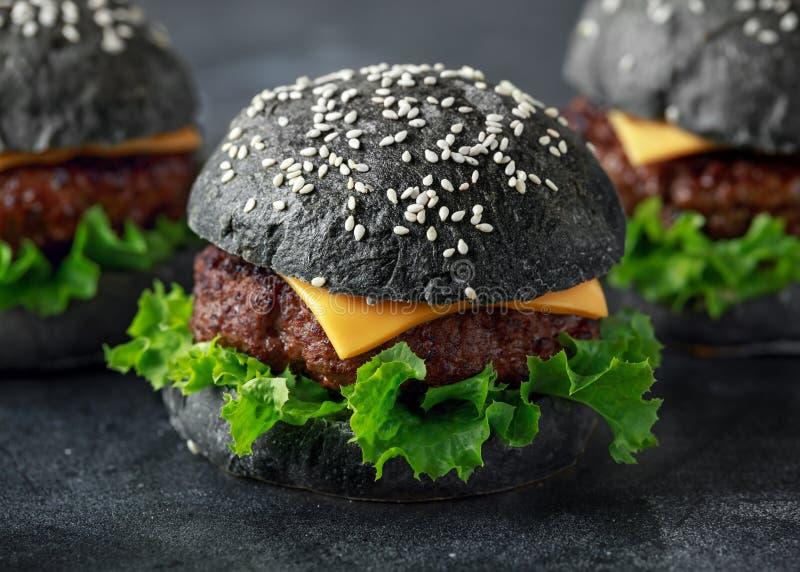 Hamburguesa negra con las hojas del queso, de la carne de vaca y de la ensalada verde Cheeseburger hecho en casa imagen de archivo