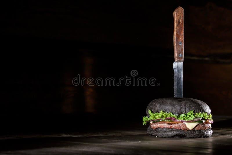 Hamburguesa negra grande, fresca en una tabla de madera Hamburguesa con la carne, el queso y las verduras fotos de archivo