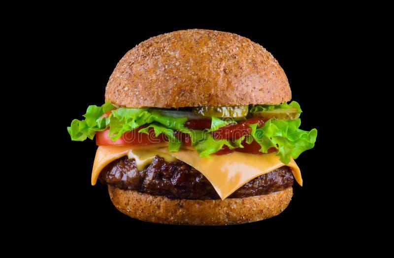 Hamburguesa o cheeseburger sabrosa grande aislado en fondo negro con la carne asada a la parrilla, queso, tomate, tocino, cebolla fotografía de archivo libre de regalías