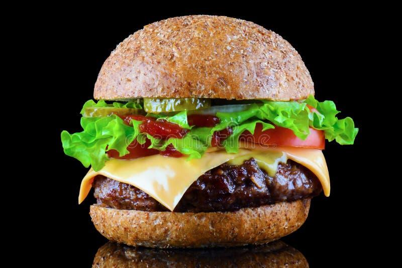Hamburguesa o cheeseburger sabrosa grande en fondo negro con la carne asada a la parrilla, queso, tomate, tocino, cebolla Primer  imágenes de archivo libres de regalías