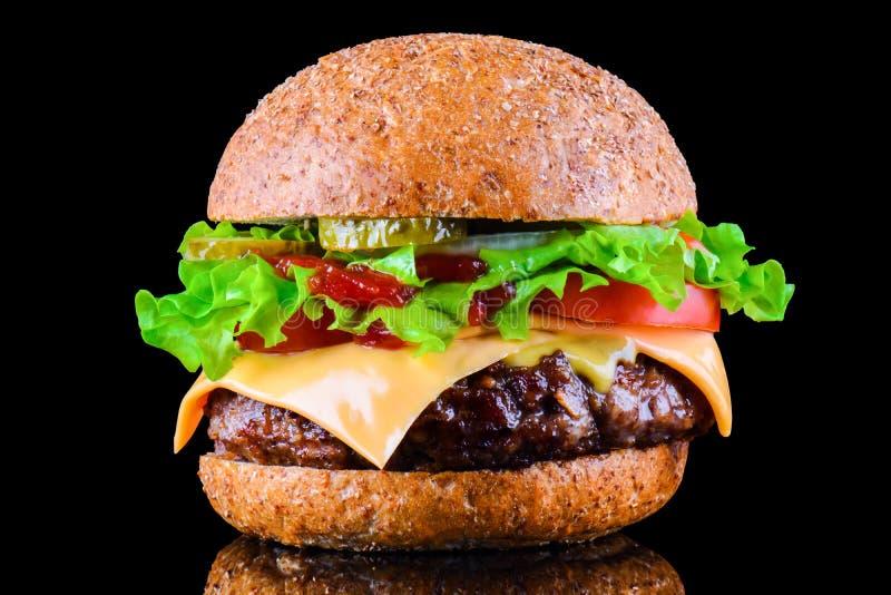 Hamburguesa o cheeseburger sabrosa grande en fondo negro con la carne asada a la parrilla, queso, tomate, tocino, cebolla Primer  fotos de archivo
