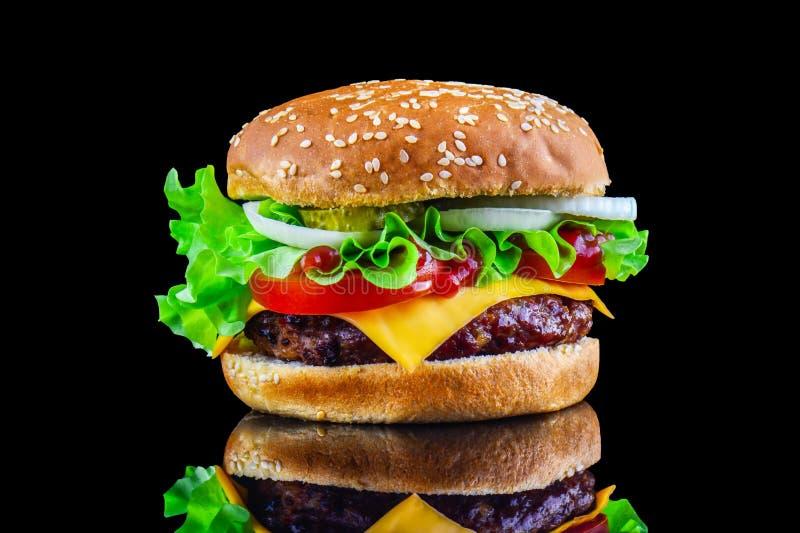 Hamburguesa o cheeseburger sabrosa grande en fondo negro con la carne asada a la parrilla, queso, tomate, tocino, cebolla Primer  fotografía de archivo