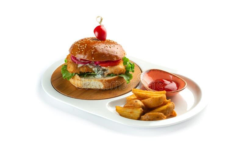 Hamburguesa, patatas fritas y salsa de tomate en una placa oval blanca aislada en el fondo blanco fotografía de archivo libre de regalías