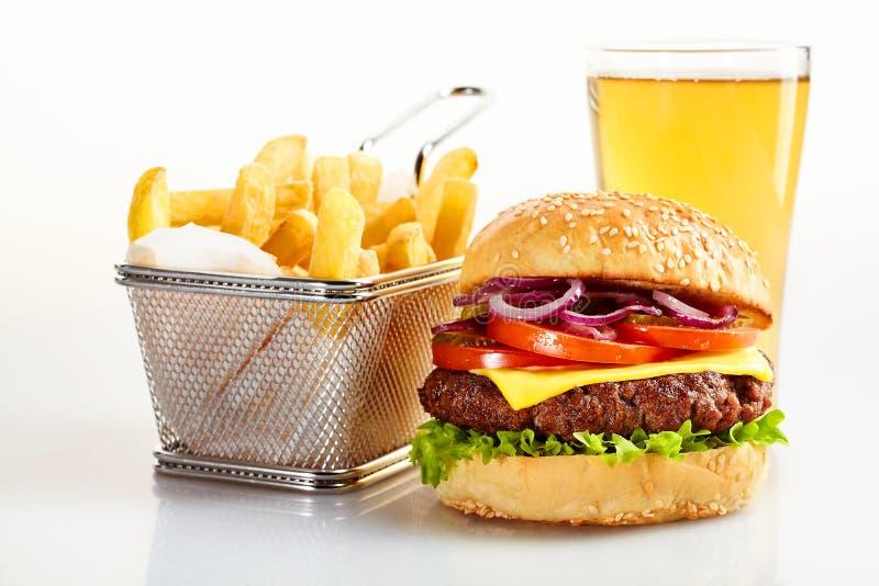 Hamburguesa sabrosa con la cesta de fritadas y de cerveza imagen de archivo libre de regalías