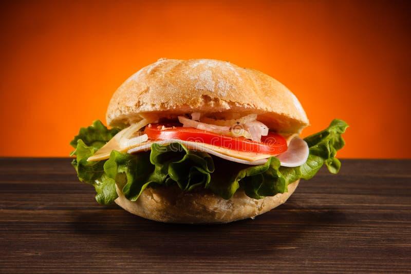 Hamburguesa sabrosa con queso y verduras imagenes de archivo