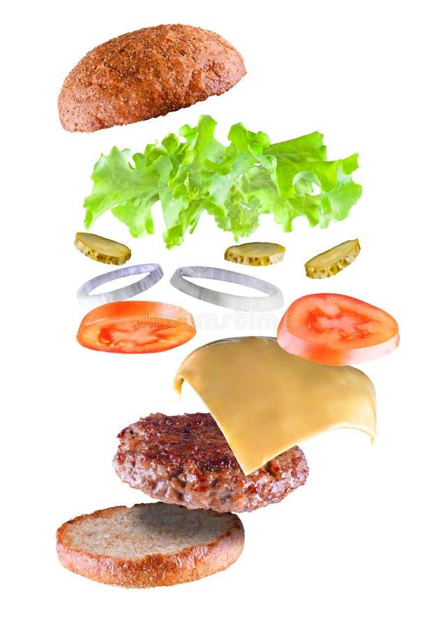 Hamburguesa sabrosa deliciosa con los ingredientes del vuelo aislados en el fondo blanco La hamburguesa parte el vuelo en aire fl foto de archivo libre de regalías