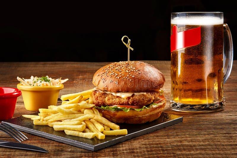 Hamburguesa sabrosa, patatas fritas con la salsa y vidrio de cerveza en tablero negro imagen de archivo libre de regalías