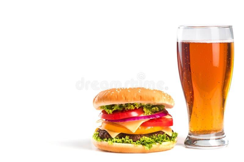 hamburguesa sabrosa y vidrio grandes de cerveza aislados imagen de archivo