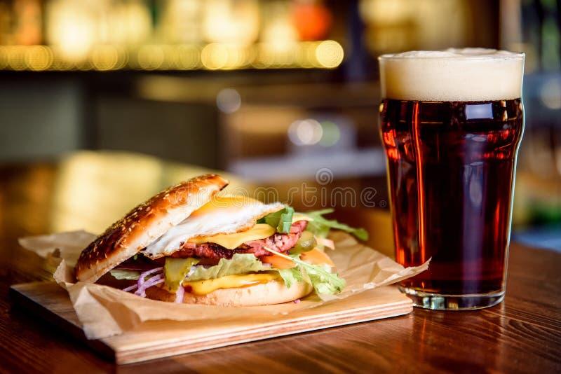 Hamburguesa y cerveza oscura en un fondo del pub imagenes de archivo