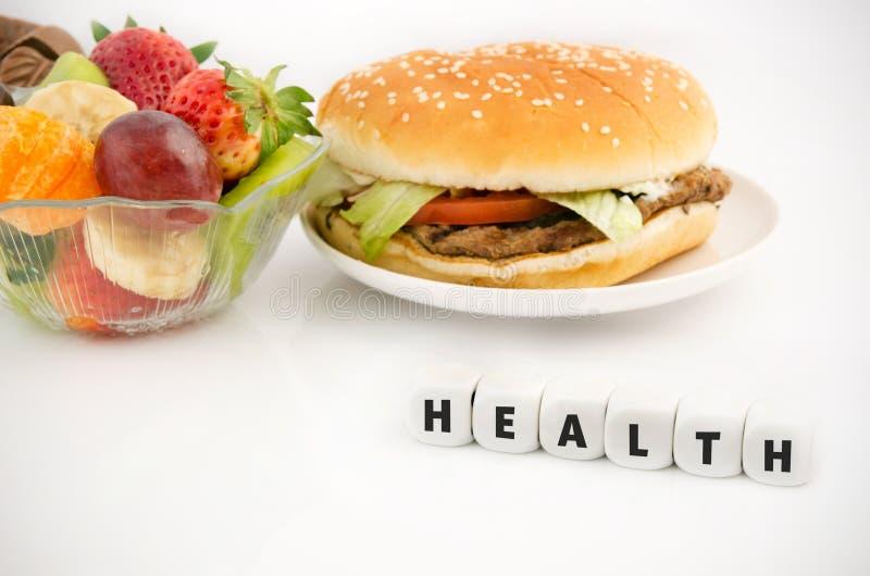 Hamburguesa y frutas en la composición de la atención sanitaria foto de archivo