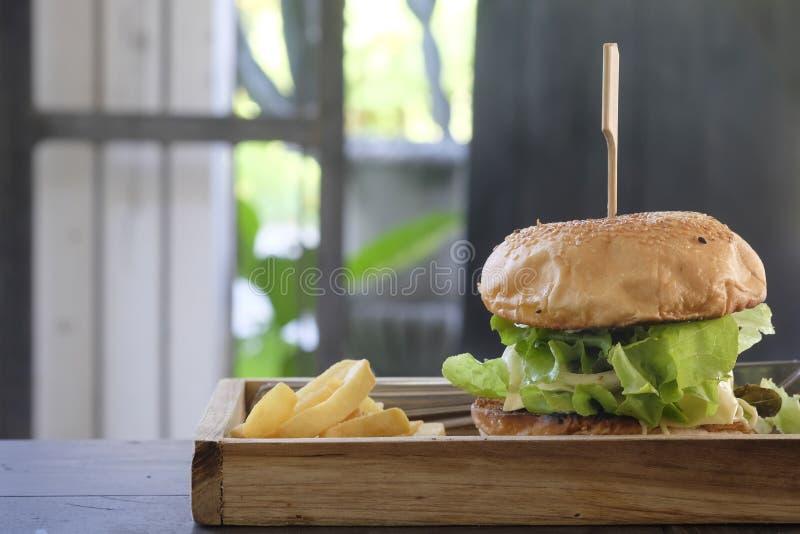 Hamburguesa y patatas fritas hechas en casa del primer en la placa de madera foto de archivo