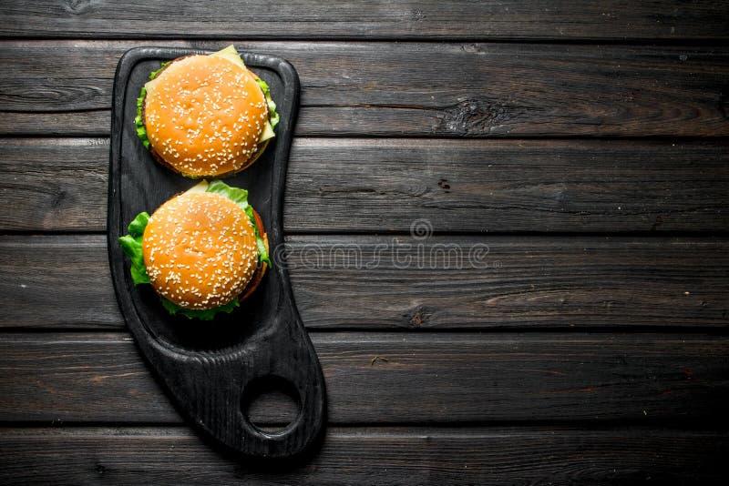 Hamburguesas con una chuleta de la carne de vaca, de verduras y del queso jugosos fotografía de archivo