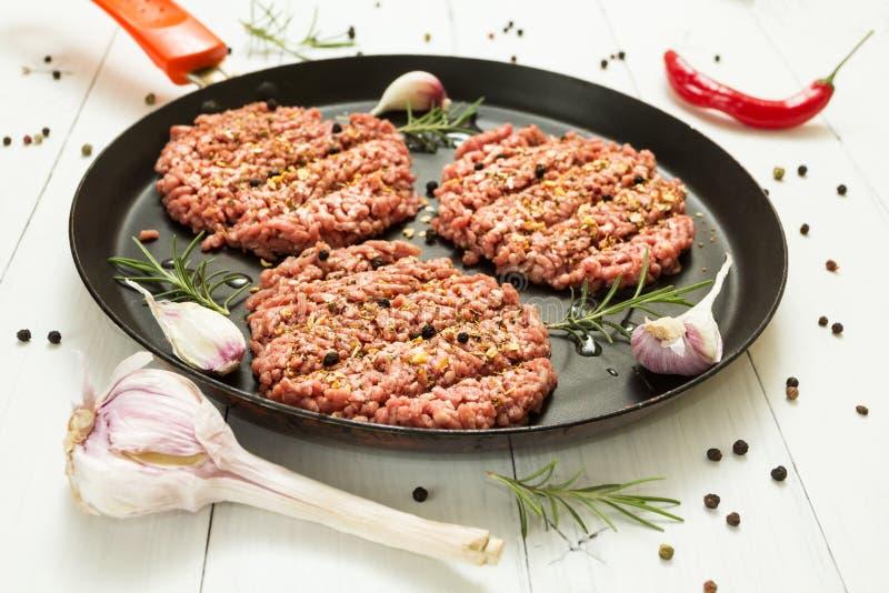 Hamburguesas crudas - chuletas de la carne orgánica de la carne de vaca con ajo, los chiles y el romero en un sartén en un fondo  foto de archivo