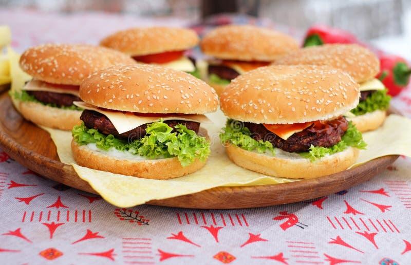 Hamburguesas de la carne de vaca y del queso con la ensalada verde y la salsa que mienten en una placa de madera en el festival d imagen de archivo libre de regalías