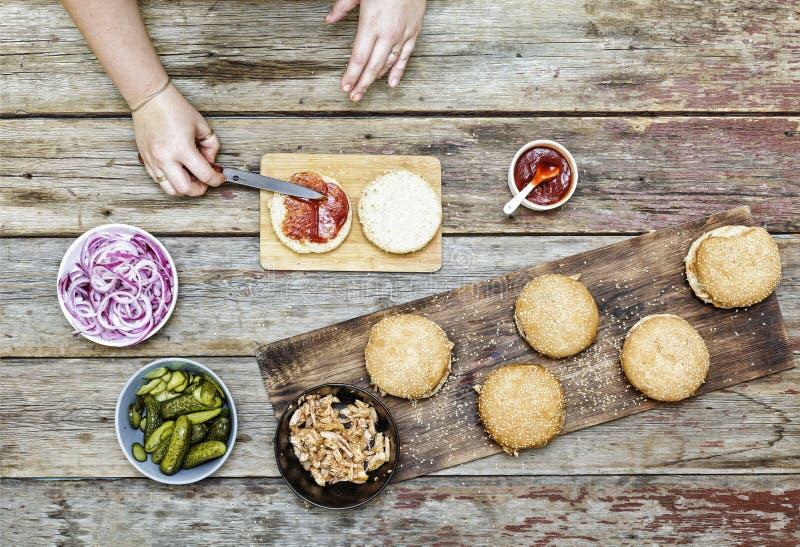 Hamburguesas de la comida, el cocinar, deliciosos, carne, pollo y verduras, recetas, manos femeninas, comiendo concepto, visión s fotografía de archivo libre de regalías