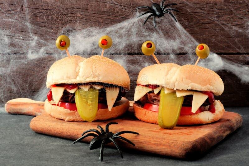 Hamburguesas del monstruo de Halloween con el fondo del web de araña imagen de archivo