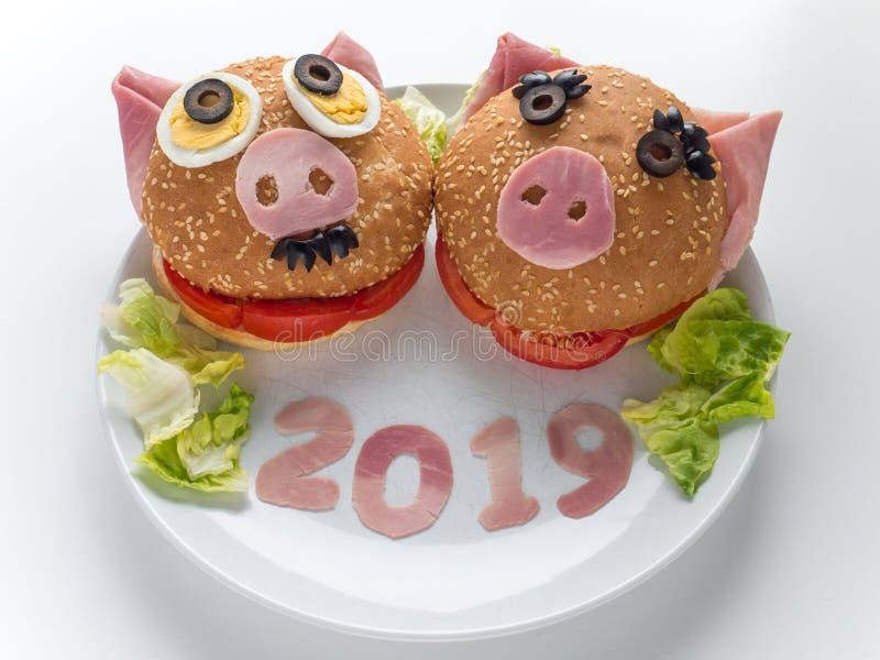 Hamburguesas divertidas del jamón del Año Nuevo de los piggies, ensalada de la lechuga y 2019 dígitos en la placa imagenes de archivo