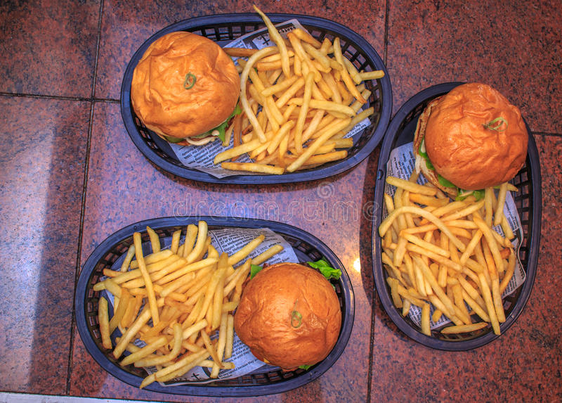 3 hamburguesas en la cesta en la casa de la hamburguesa imagen de archivo