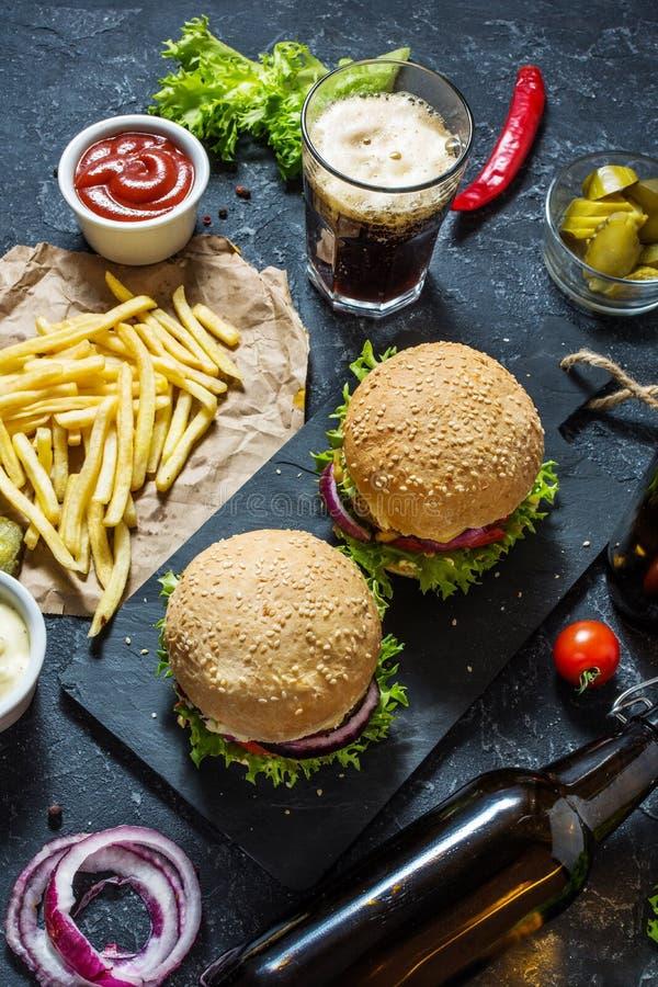Hamburguesas hechas en casa con carne de vaca y patatas y vidrio fritos de cerveza oscura fría en la tabla de piedra imágenes de archivo libres de regalías