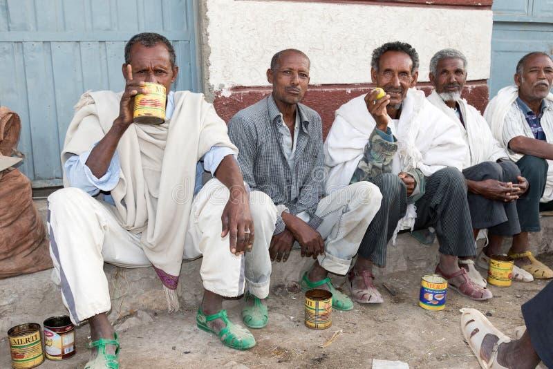 Hamd Ela, Etiopien, Februari 23 2015: Etiopiska män sitter yttersidan i gatan som talar, och dricka en lokal drink från gammalt t royaltyfria foton
