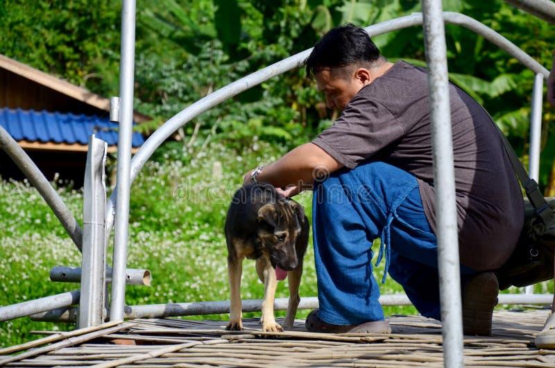 Hameçon de aide de mouvement d'homme thaïlandais de dos de chien photo stock