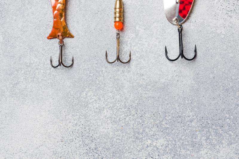 Hameçons et amorces dans un ensemble pour pêcher les poissons différents sur un fond gris avec l'espace de copie Configuration pl photographie stock