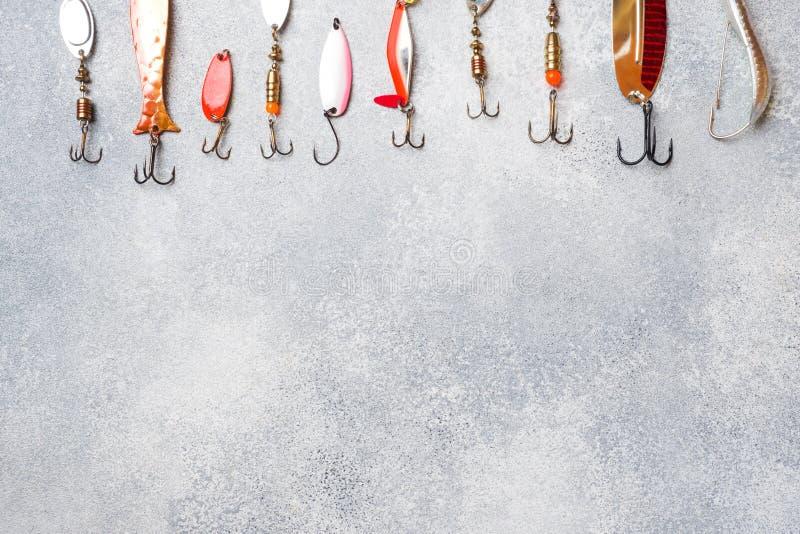 Hameçons et amorces dans un ensemble pour pêcher les poissons différents sur un fond gris avec l'espace de copie Configuration pl images stock