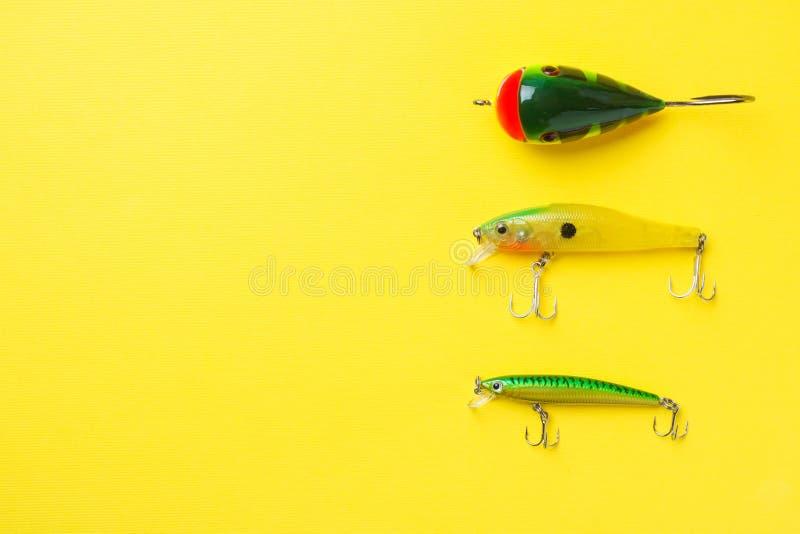 Hameçons et amorces dans un ensemble pour pêcher les poissons différents sur un fond jaune avec l'espace de copie Configuration p images stock