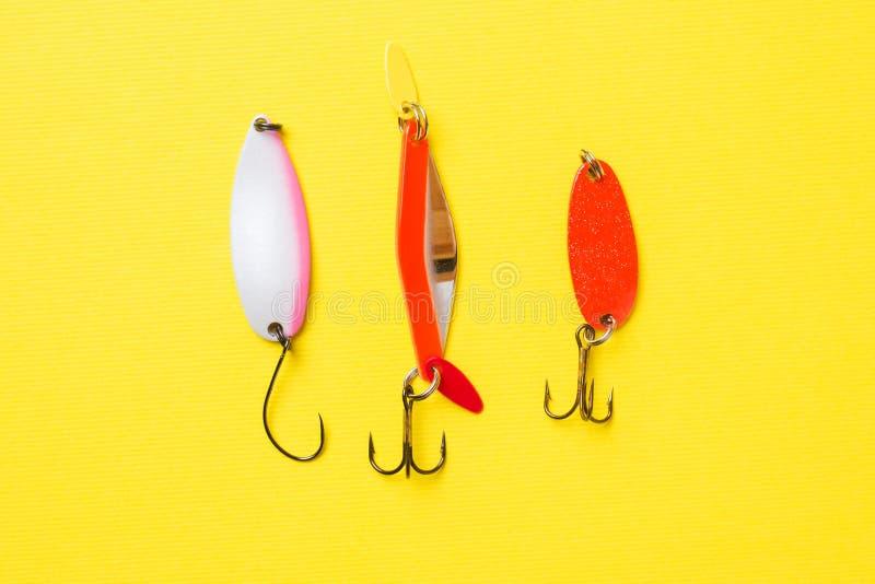 Hameçons et amorces dans un ensemble pour pêcher les poissons différents sur un fond jaune avec l'espace de copie Configuration p image libre de droits