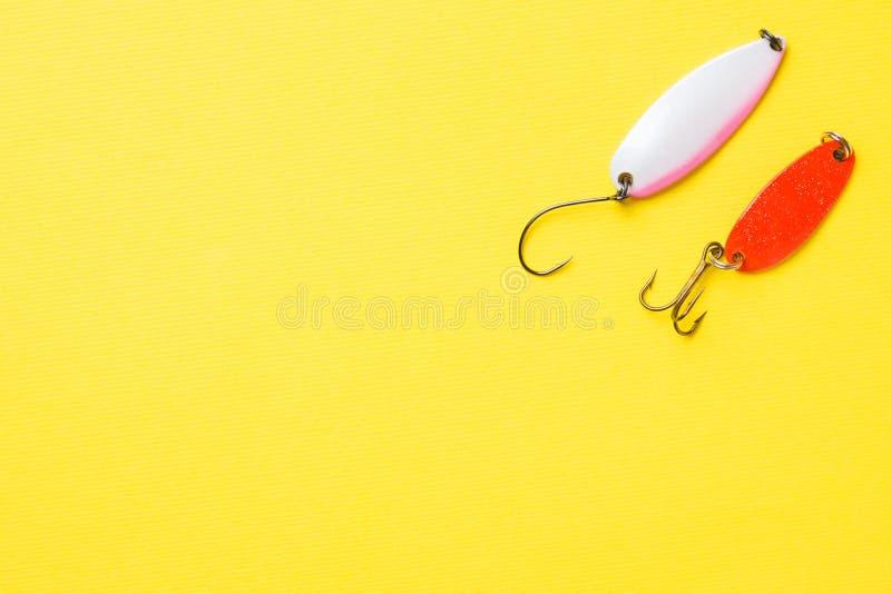 Hameçons et amorces dans un ensemble pour pêcher les poissons différents sur un fond jaune avec l'espace de copie Configuration p photo libre de droits