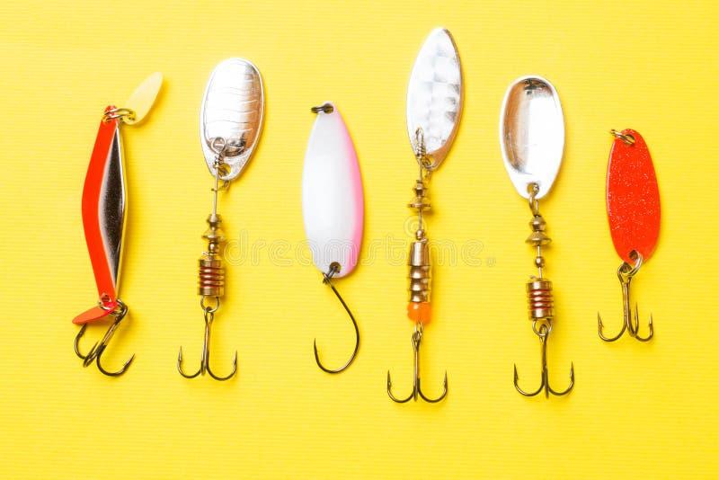 Hameçons et amorces dans un ensemble pour pêcher les poissons différents sur un fond jaune avec l'espace de copie Configuration p image stock