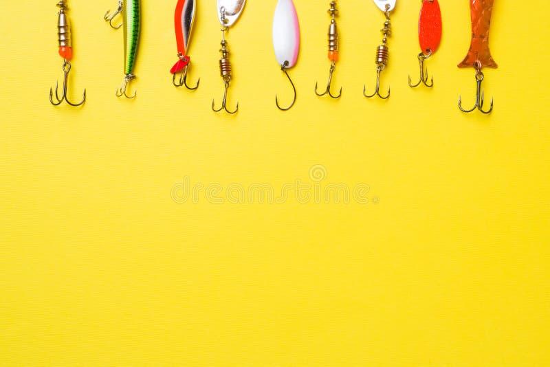 Hameçons et amorces dans un ensemble pour pêcher les poissons différents sur un fond jaune avec l'espace de copie Configuration p images libres de droits