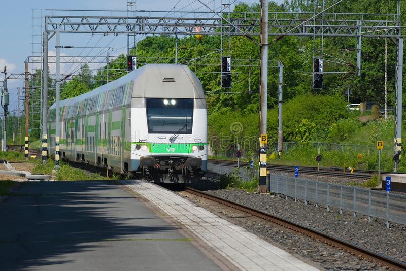 Modern double-Decker train coming to the platform of the railway station, Hameenlinna, Finland. HAMEENLINNA, FINLAND - JUNE 10, 2017: Modern double-Decker train stock photos