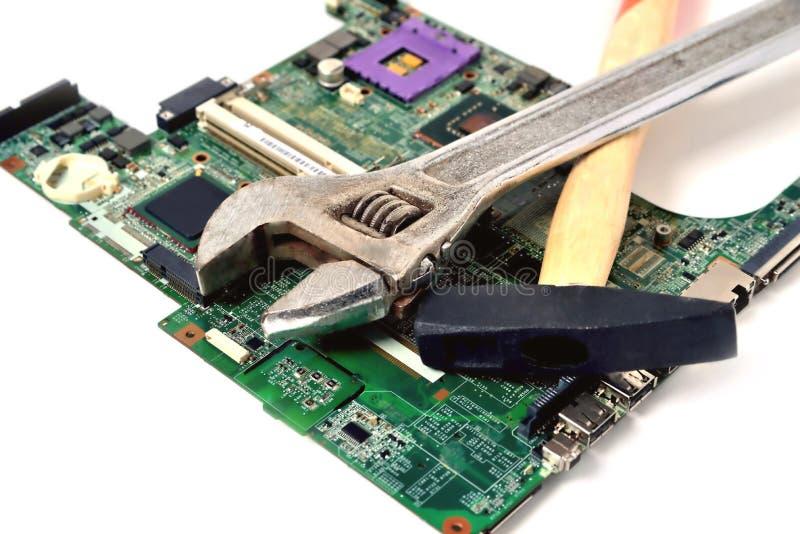 Hamer en moersleutel op een oude microschakeling voor een computer op een whi royalty-vrije stock fotografie