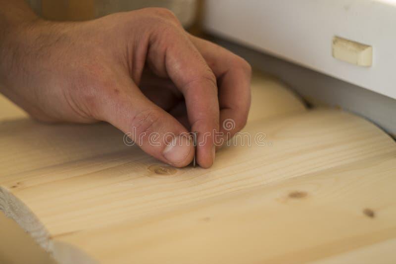 Hamer en Spijker die op houten bokehachtergrond gebruiken stock fotografie