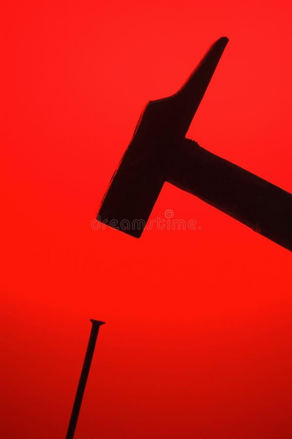 Hamer en spijker met rode backlight royalty-vrije stock afbeeldingen