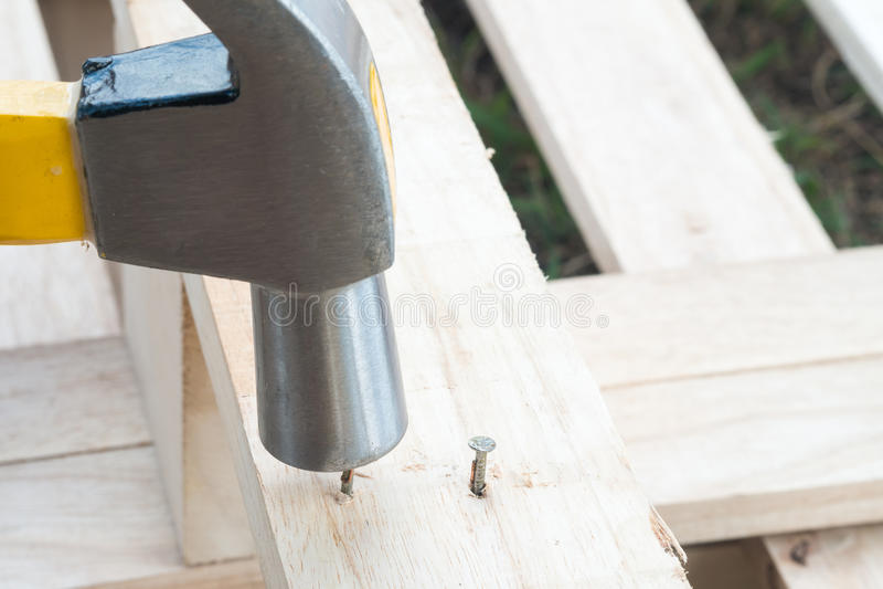 Hamer en spijker op hout stock foto