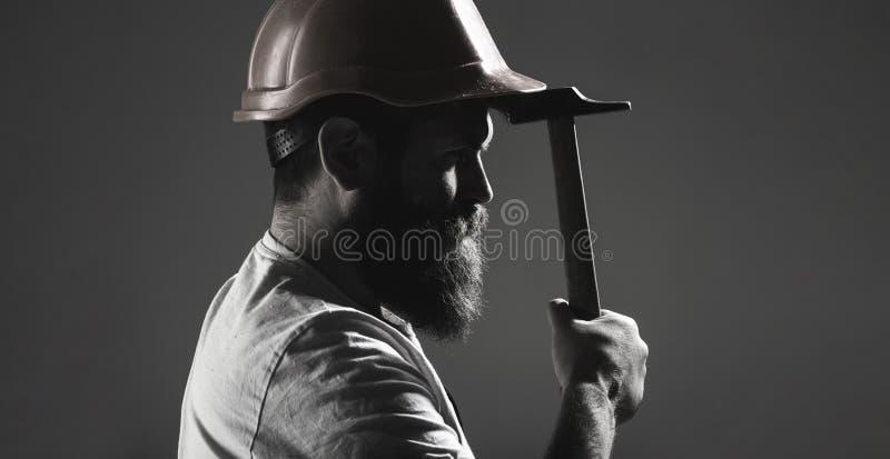 Hamer het hameren Bouwer in helm, hamer, manusje van alles, bouwers in bouwvakker De manusje van allesdiensten de industrie, bouw royalty-vrije stock afbeeldingen
