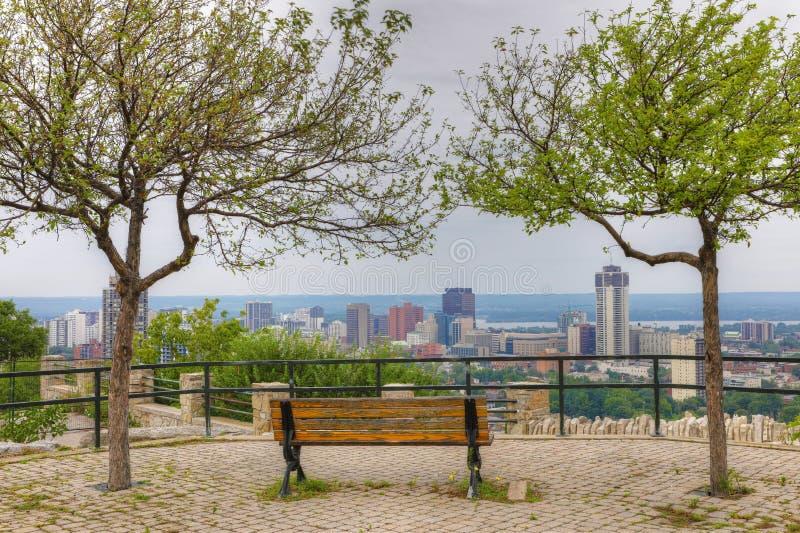 Hamilton Kanada med parkerar bänken i förgrund arkivfoto