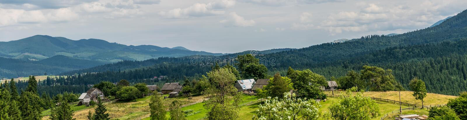 Hamlet in Carpathian Mountains panorama. Panoramic view to village and forests. Modest houses of small hamlet in Carpathian Mountains, Ukraine. Peasant life in a stock photo