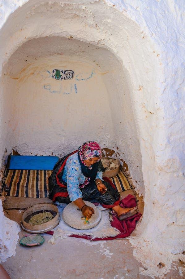 HAMMAMET, TUNÍSIA - em outubro de 2014: A mulher está moendo a grão na casa do berber o 7 de outubro de 2014 fotografia de stock royalty free