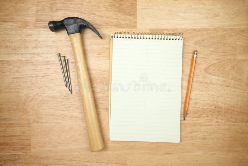 hammaren spikar den paper blyertspennan för blocket arkivbild