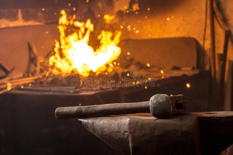 Hammer on anvil with fire of burning coal in background.  stock photo