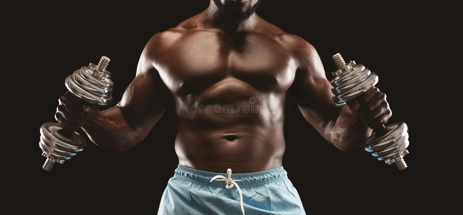 Hammer curls with both hands over black studio background. Cropped image of black guy making hammer curls with both hands over black studio background, panorama stock photos