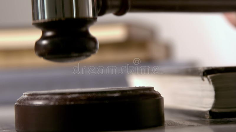 Hammer, der auf das Klingen des Blockes neben Büchern fällt stock footage